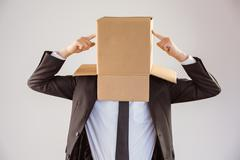 Anonymous businessman pointing to box - stock photo