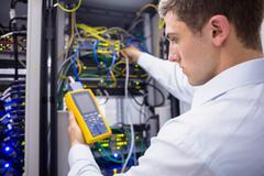 Serious technician using digital cable analyzer on server Stock Photos