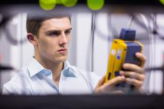 Serious technician using digital cable analyzer on server - stock photo