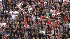 Stock Video Footage of 18. Football. Soccer. Fans cheering, singing and jumping on the stands. Zoom out