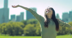Young Asian Woman feeling refreshed in a park 4k - stock footage