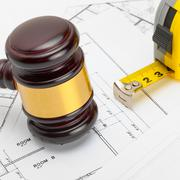 Wooden judge gavel with measure tape above construction blueprint - studio sh Stock Photos