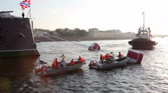 Motorboats with riggers are near Aurora`s tow-ropes on Neva river Stock Footage