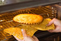 woman taking fresh pie out of oven at home in the kitchen - stock photo