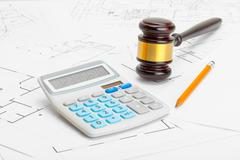 Wooden judge gavel with calculator and pencil over construction blueprint - s Stock Photos