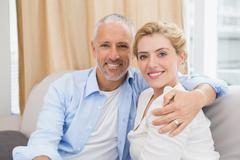 Happy couple smiling at camera on sofa - stock photo
