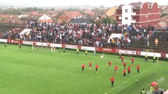 Football team running for warm up before soccer match, fans on stadium stands. - stock footage