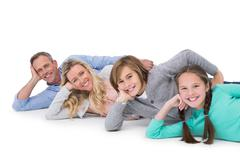 Smiling family lying on the floor in row Stock Photos
