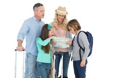 Stock Photo of Tourist family consulting the map