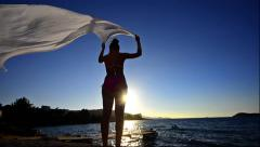 Beautiful young woman on the beach at sunset with a colored tissue scarf, slo Stock Footage