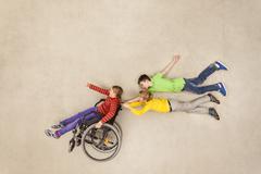 Children having fun with handicapped friend - stock photo