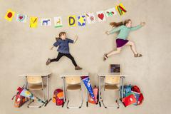 School kids chasing in class room Kuvituskuvat