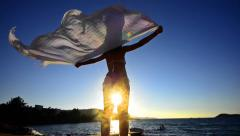 silhouette of dancing woman sith scarf on the beach wind, inspiration,slow mo - stock footage
