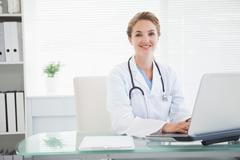 Doctor smiling as she types - stock photo