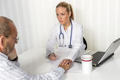 Doctor consooling patient in medical practice Stock Photos