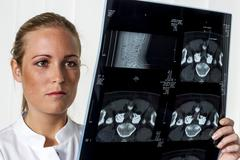 Doctor looking at MRI image - stock photo