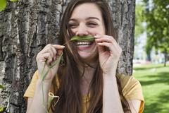 Portrait of young woman holding spike in her face like a moustache Stock Photos