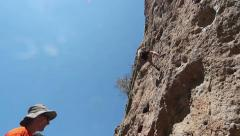 Rock Climber Rappelling Down a Sheer Cliff from Below at Malibu Creek State Park Stock Footage