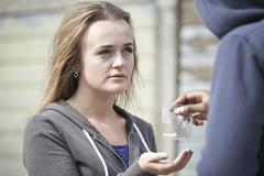 Teenage girl buying drugs on the street from dealer Stock Photos