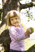Portrait of smiling little girl sitting on an apple tree with bitten apple - stock photo