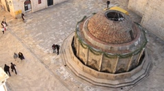 Tourists walking around fountain at old town castle in Dubrovnik Stock Footage