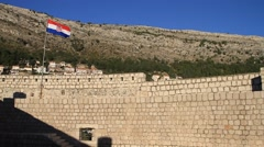 Flag and old city castle fort wall of Dubrovnik in Croatia Stock Footage
