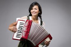 Portrait of smiling young woman playing accordion - stock photo