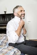 Stock Photo of Portrait of smiling businessman binding tie in his bedroom