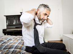 Businessman binding tie in his bedroom - stock photo