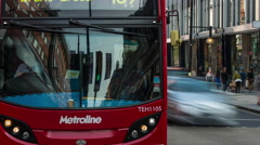 Red buses and black London taxis on a busy road in London Stock Footage