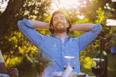 Man leaning back and smiling at dinner in evening light Stock Photos