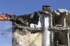 demolition equipment knocking down an old multi-family house - stock photo