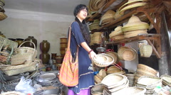 Young lady picking and choosing handmade bamboo weaving crafts in the store Stock Footage