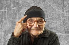 Stock Photo of elderly woman has an idea, pointing with finger on her head.