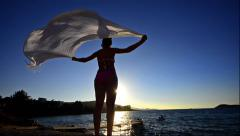 Beautiful young woman on the beach at sunset with a colored tissue scarf, fre Stock Footage