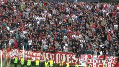 Football fans jumping and cheering. Zoom out and pan left on derby soccer match. Stock Footage