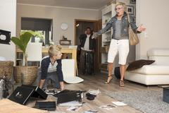 Family watching chaos after burglary when coming back in their one-family house Stock Photos