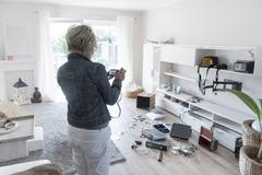 Woman photographing chaos after burglary when coming back in her one-family - stock photo