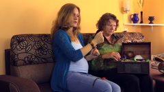 Granny show her pregnant granddaughter jewelry from retro chest Stock Footage