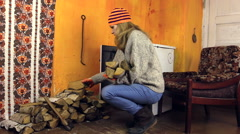 Girl with orange hat bring wood, sit in chair bask hand of stove Stock Footage