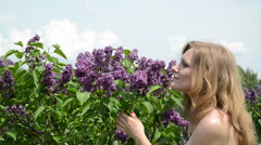 Girl smell lilac tree blooms and smile with satisfaction Stock Footage
