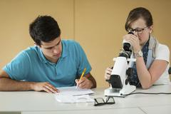 Vocational school students using optician device - stock photo