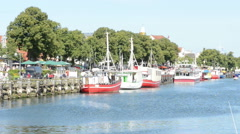 Fisher boats in harbor and  People visiting stores Stock Footage