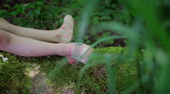 Closeup Of Little Girls Legs (Laying On A Log) In A Beautiful Forest Stock Footage