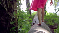 Little Girl Walks, Then Runs, Down A Log (Away From Camera) Stock Footage