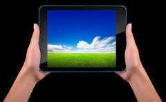 Tablet computer with blue sky and green grass - stock photo