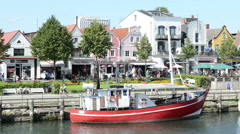 People visiting harbor with boats and stores Stock Footage