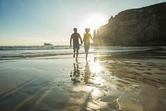 France, Brittany, Camaret-sur-Mer, teenage couple running on the beach - stock photo