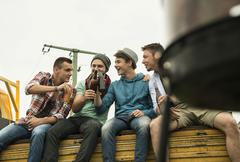 Group of friends drinking beer on pick-up truck Stock Photos