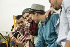 Group of friends with cell phone on pick-up truck Stock Photos